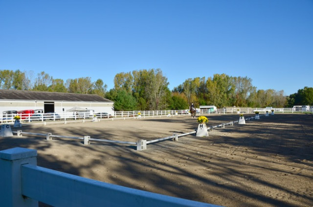 Early morning long shadows slice across the dressage ring.