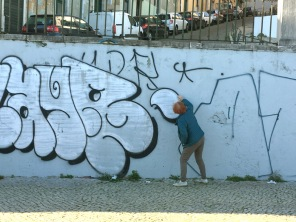 Alli makes like the graffiti artist she isn't. There's a LOT of graffiti in Lisbon.